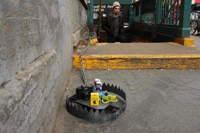 "Jeff Greenspan and Hunter Fine have been installing ""Hipster Traps"" around New York City which include sunglasses, a yellow bicycle chain, a Holga camera, a can of PBR and a pack of American Spirits as bait."