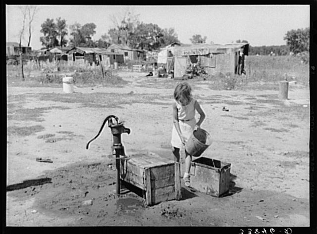 Girl gets water at Mays Avenue Camp on the flats of the North Canadian River, 1934